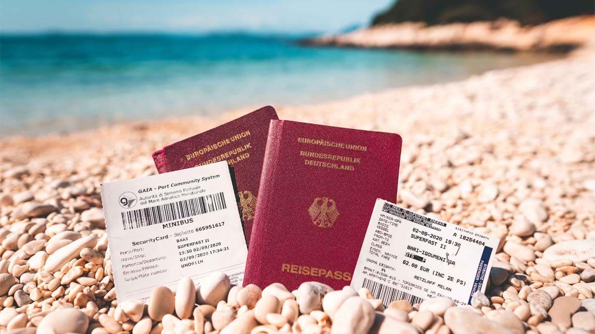 Reisepass mit Fährtickets am Strand für die Einreise nach Griechenland